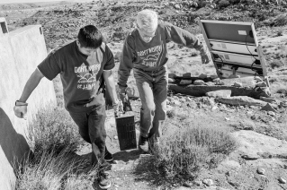 Paul Tso and Joseph Day haul an old battery off for proper disposal. A good portion of homes on Hopi do not have electricity and have relied on batteries and generators in the past, and, increasingly now, solar panels. © Tomas Muscionico