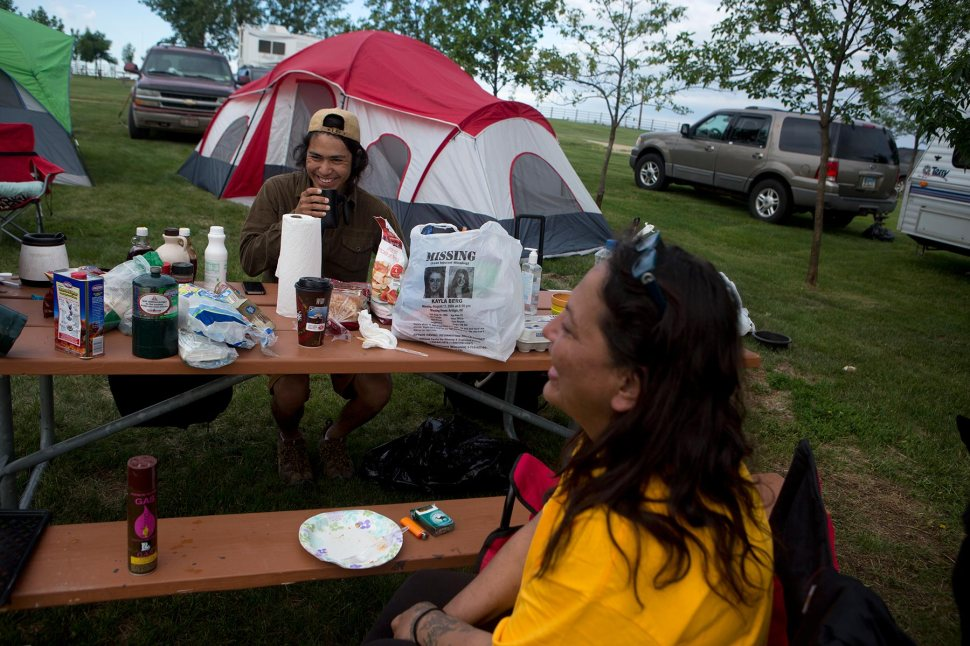 In this June 13, 2015 photo, Kalen Goodluck, left, and Lissa Yellowbird-Chase visit over morning coffee in their last few hours at the campsite before packing up and heading home after a weekend of searching for any signs of a body. © Kristina Barker