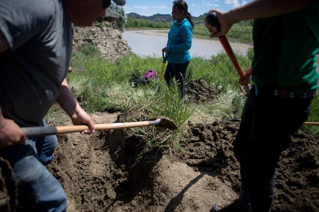In this June 13, 2015 photo, Leslie Barrett, left, Lissa Yellowbird-Chase, and Kalen Goodluck slowly dig away at the bank of the Little Missouri River. © Kristina Barker for Al Jazeera America